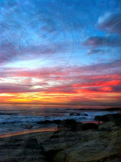 sunset clouds red orange ocean waves  photo