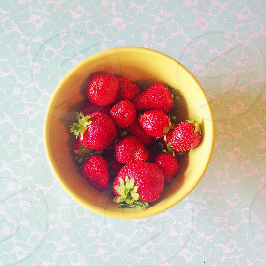 strawberries in yellow plastic bowl photo