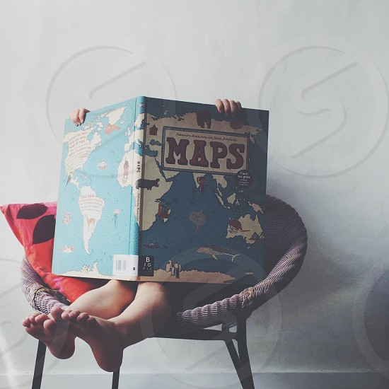 person holding blue and white MAPS book sitting on gray wicker chair photo