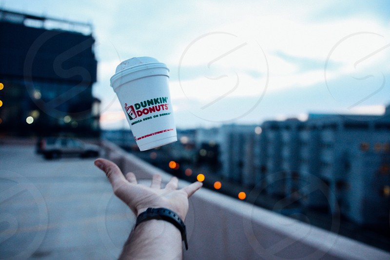 person tossing up white dunkin donuts soda cup photo