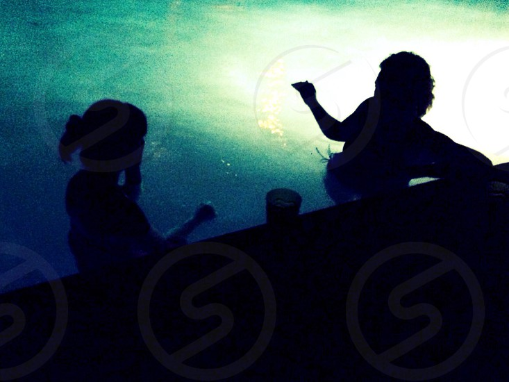 people standing in swimming pool at night with pool light on photo