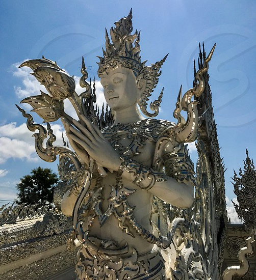 Outdoor day vertical portrait colour Wat Rong Khun The White Temple Chiang Rai Thailand Thai Kingdom of Thailand travel tourism tourist wanderlust summer summertime temple Buddhist Buddhism spiritual pure holy dragon monster carved ornate elaborate art modern sculpture sculpted east eastern hands silver mirror mosaic magical mythical blue sky contrast goddess Buddha face photo