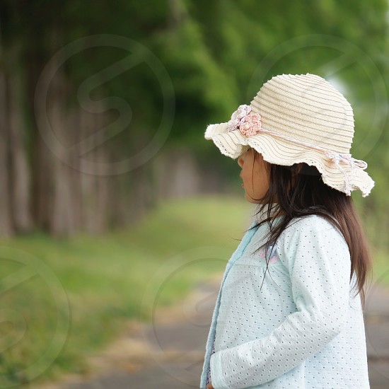 girl in blue eyelet jacket and white hat photo