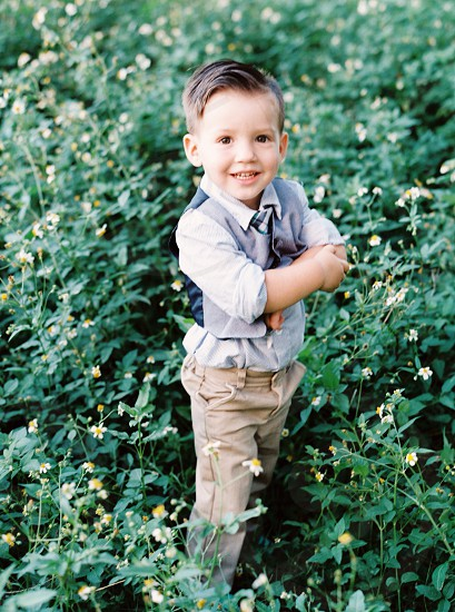 boy in grey and blue button up vest standing photo