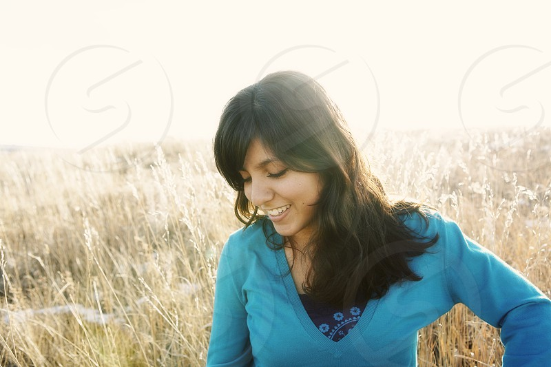 woman in blue v neck sweatshirt looking down smiling photo