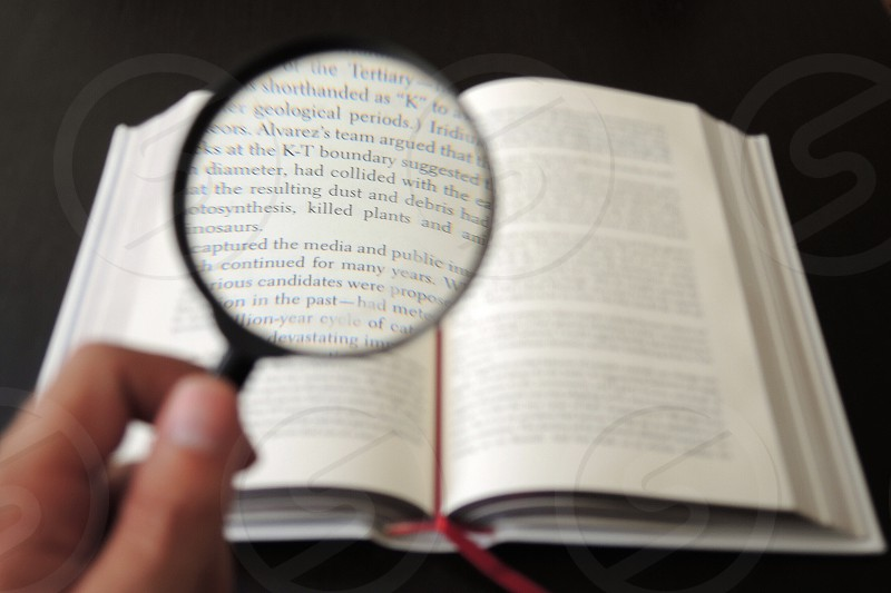 person using a magnifying glass to a read a book photo
