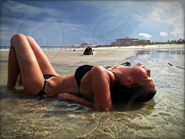 woman wearing black brassiere lying on seashore photo