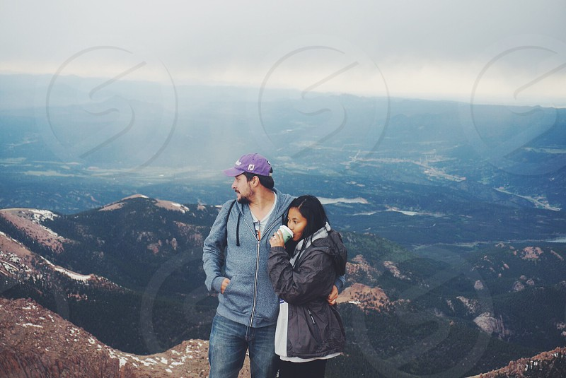 man and woman wearing jacket standing on mountain cliff during daytime photo