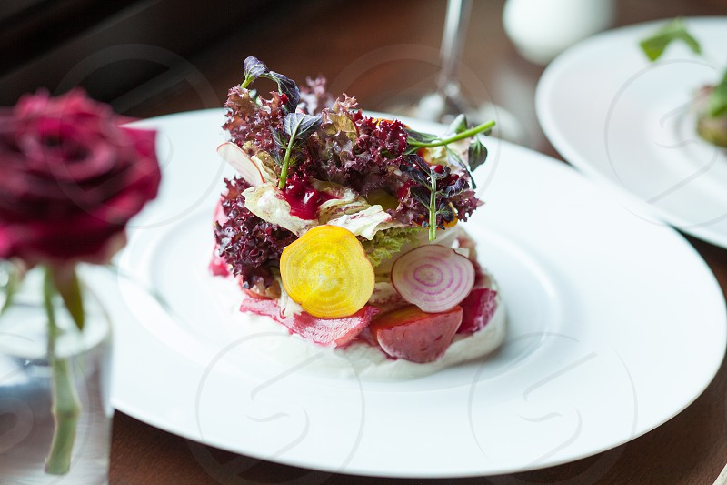 maroon coriander with lettuce and onion dish on white dining plate beside rose center piece photo