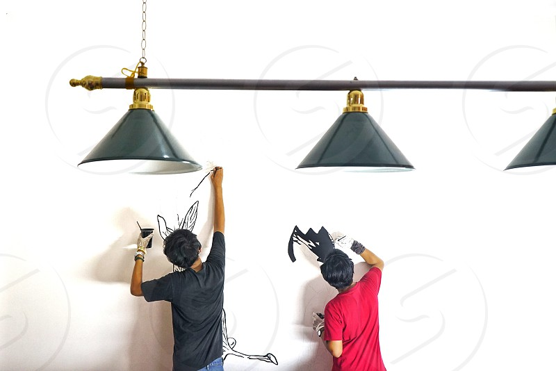 2 men paint the wall under 3 pendant lamp photo