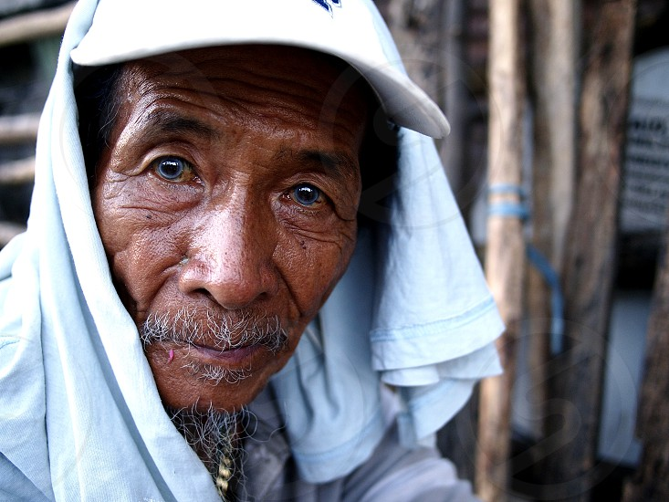 ANTIPOLO CITY PHILIPPINES - NOVEMBER 24 2018: An old Asian man rests and looks at the camera at a sidewalk along a busy street. photo