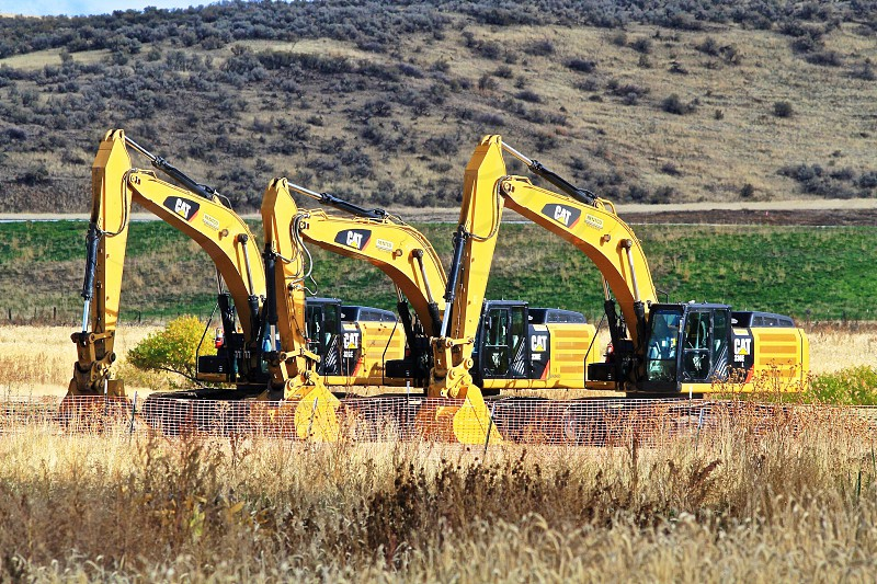 3 yellow and black excavators on green grass during daytime photo