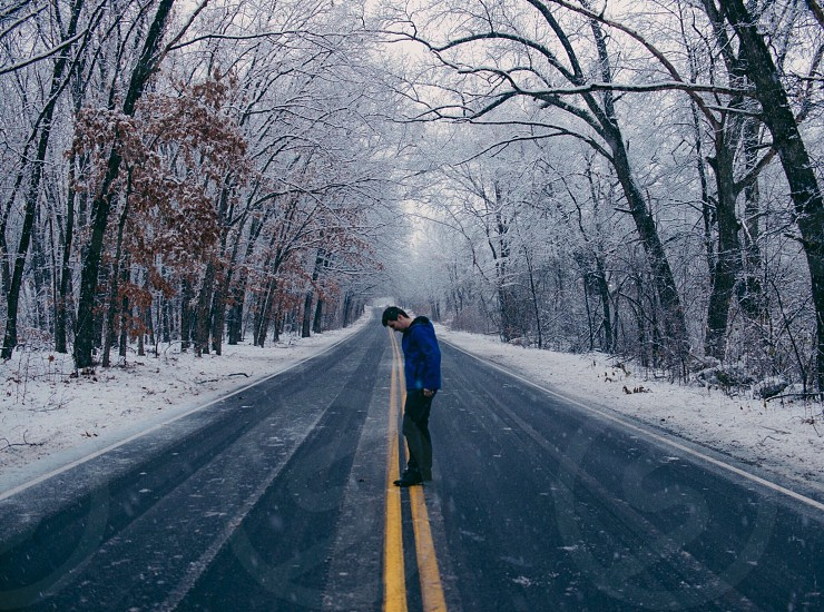 man in blue sweat shirt in the middle of the road photo