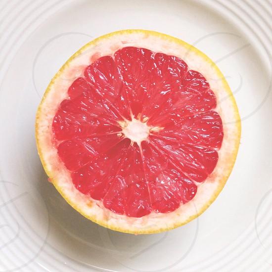 pink grapefruit halved on plate photo