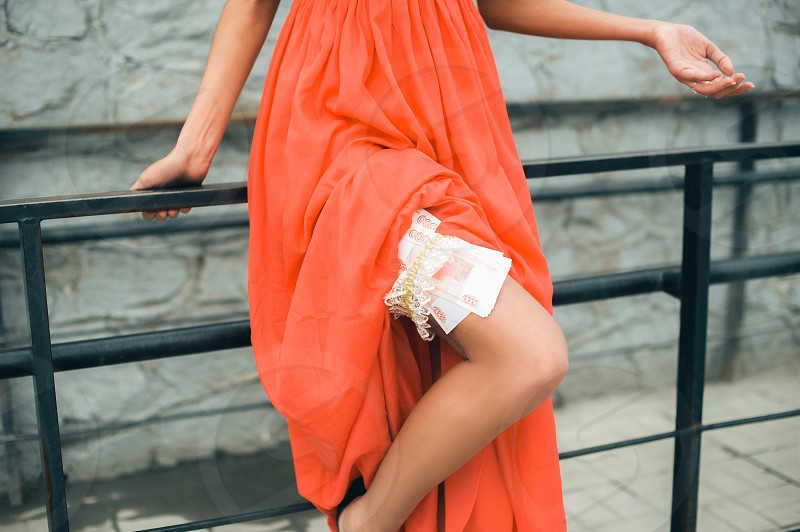 young girl in a red dress. revealing legs earns money photo