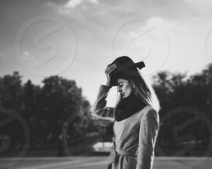 woman in coat standing while holding her round hat in grayscale photography photo