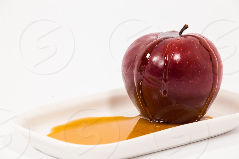 Red apple with drops of honey on white plate with honey isolated on a white background. Symbols of Jewish New Year - Rosh Hashanah.   photo