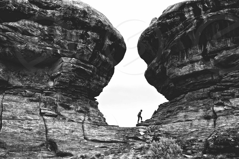 person in the middle of a rock formation photo