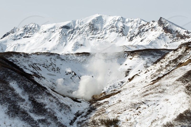 Volcano landscape of Kamchatka Peninsula. Scenery winter view of geothermal valley of Dachnye Hot Springs: popular touristic attraction in volcanic zone of active Mutnovsky Volcano on Russian Far East photo