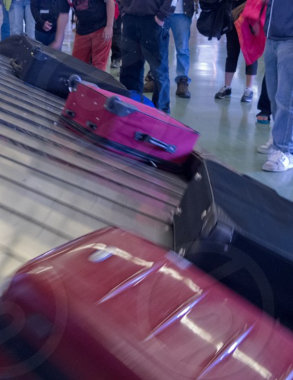 Airport baggage claim passengers wait for their luggage on conveyor belt after flight landing photo