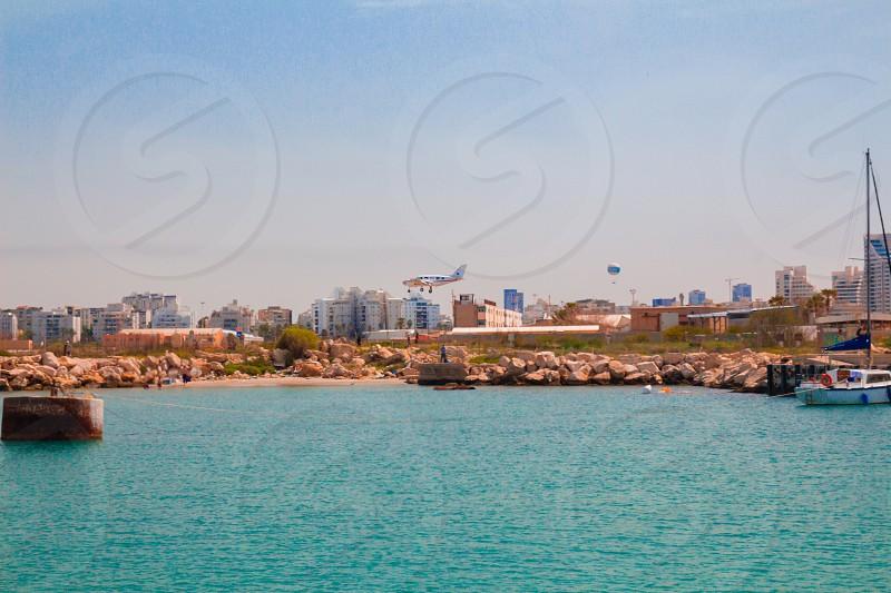 Light aircraft landing above the sea. Mediterranean coast Tel Aviv Israel. photo