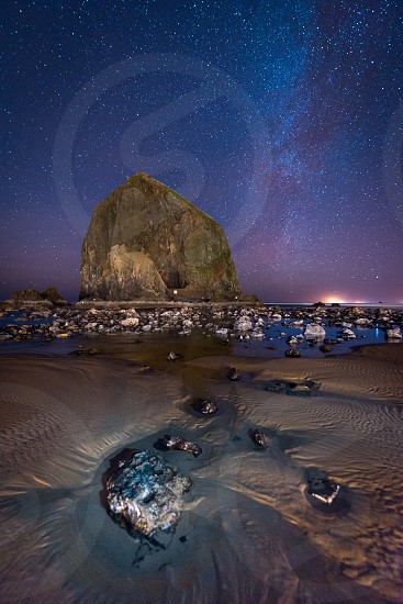 view of the beach at night next to a large rock photo