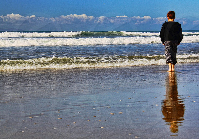 Seen from behind a little boy stands at the edge of the ocean on a sandy beach photo