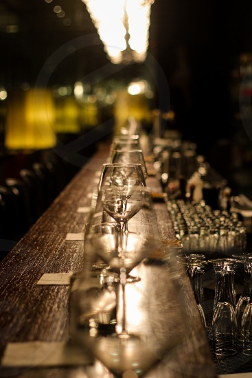 wine glasses lined up on a wood bar photo