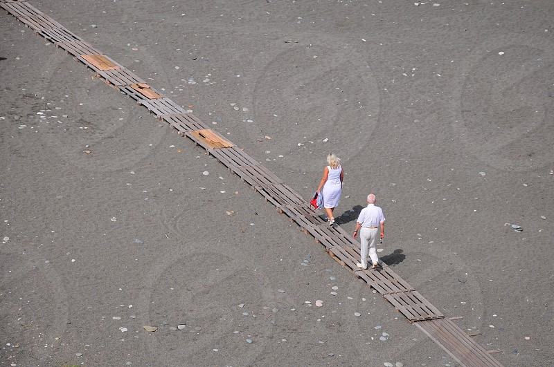 man and woman walking on wooden path photo