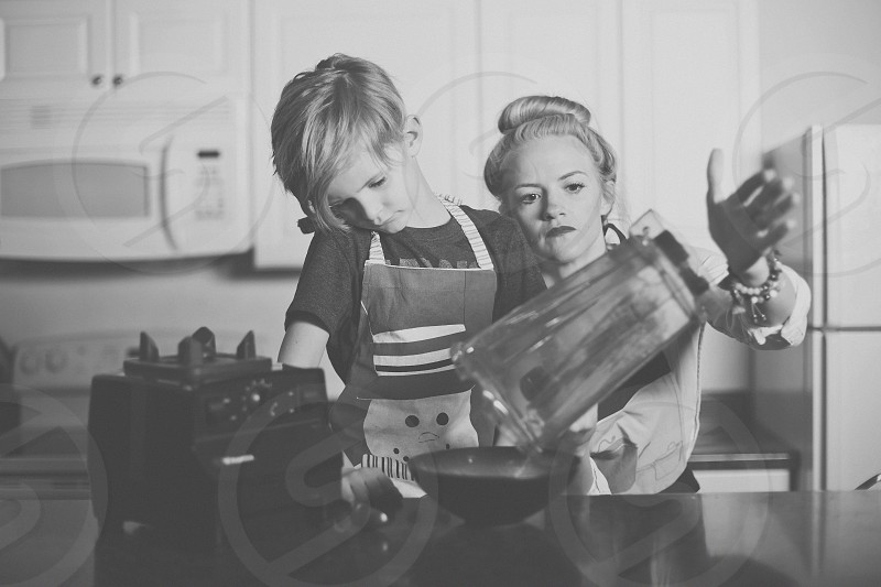 greyscale photography of child pouring blended substance on bowl beside woman photo