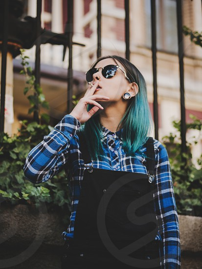 Young attractive punk girl smoking cigarette. Hipster with blue unusial dyed hair piercing in nose violet lenses ears tunnels on empty European old street. photo
