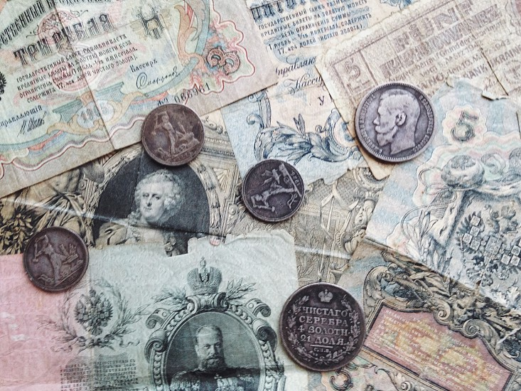 silver round coins on top of banknotes photo