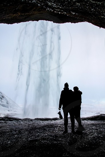two people standing in a cave behind a crashing waterfall photo