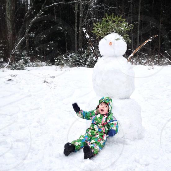 baby sitting near snowman photo