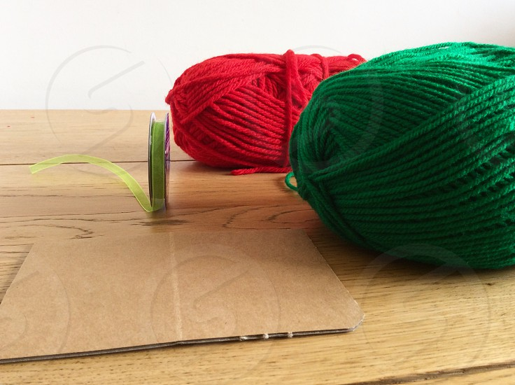 Balls of red and green wool and ribbon. Items to make  a homemade toy photo