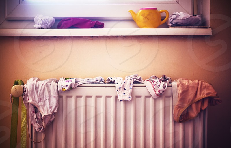 Details of everyday family life wet children's underwear on radiator. photo