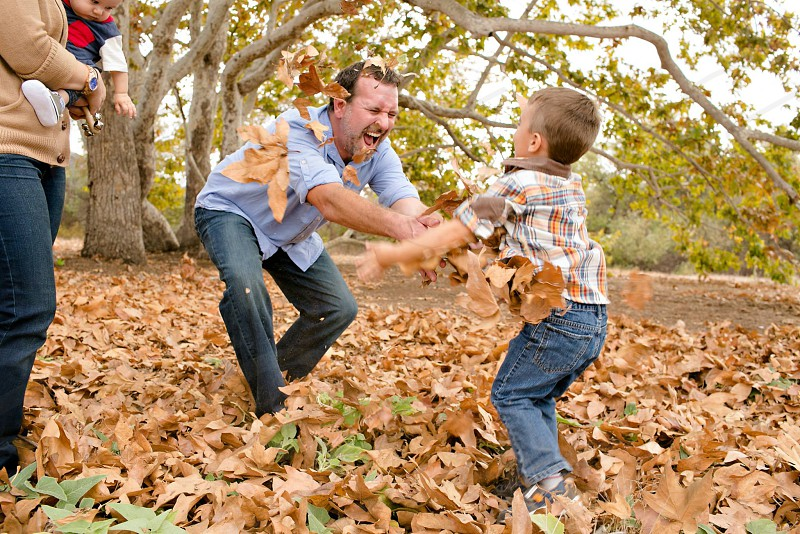 man with a child playing in dried leaves photo