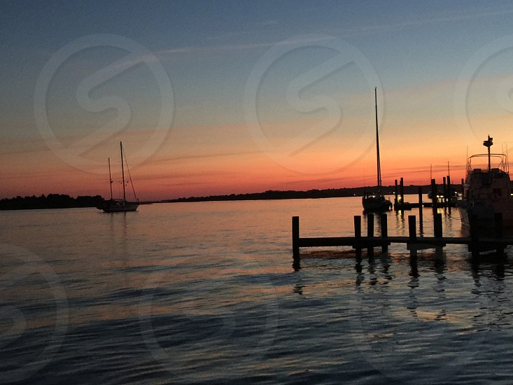 Water ocean river pier dock boat sunset photo