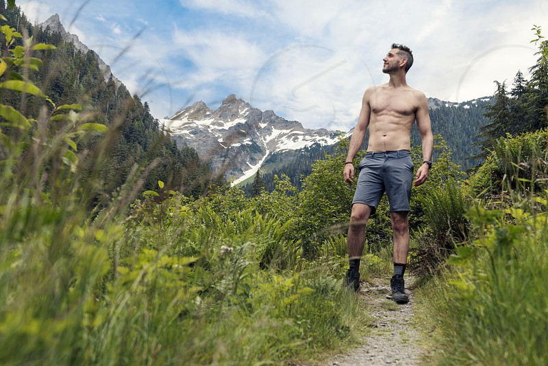 Shirtless muscular man hiking on trail looking into the distance. photo