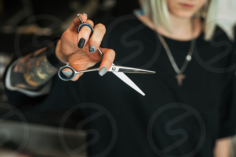 Girl sit on the chair and hold scissors in Barber Shop. - Image photo
