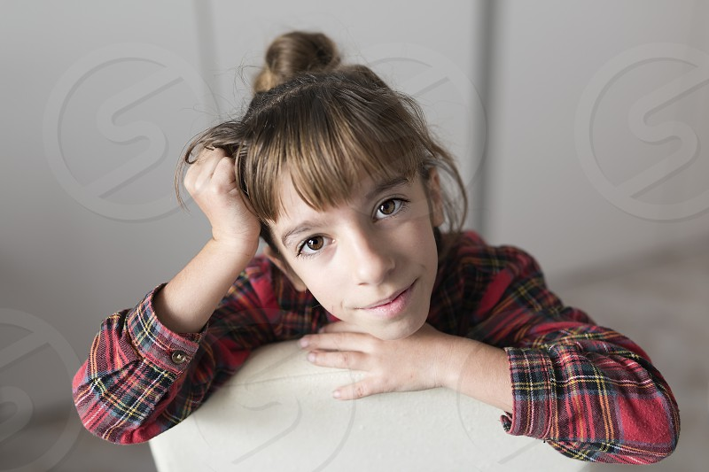 Portrait of a 10 year old girl sitting on a chair. Horizontal shot photo