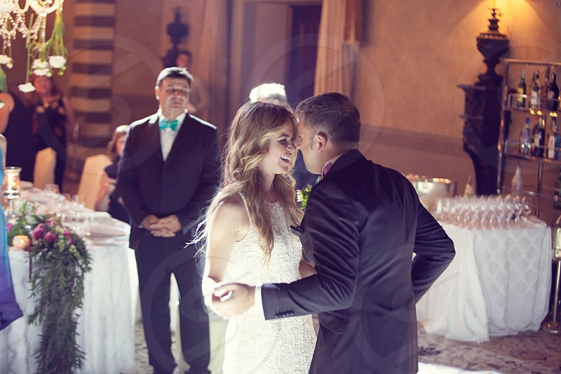 smiling blonde bride in white dancing with the groom on the dance floor as people watch photo