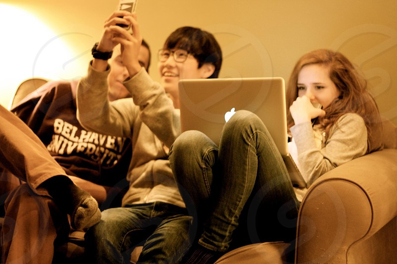 two boys and a girl seated on a sofa looking at a phone and a laptop photo