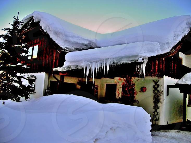 Snow-covered house and icicles in sunrise photo