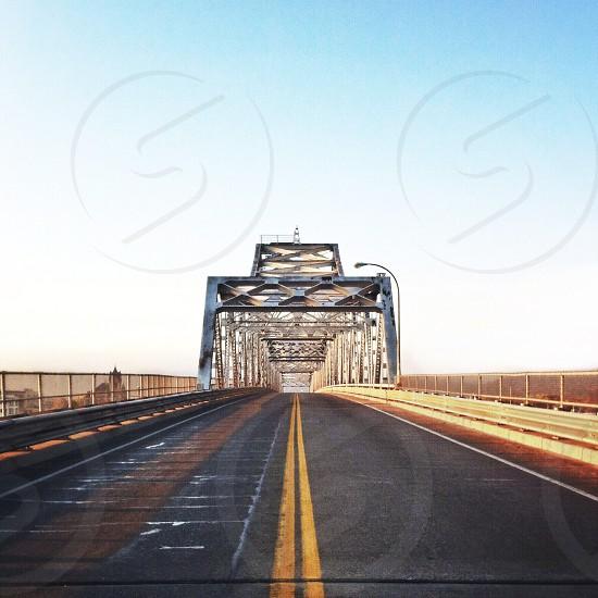 view of asphalt rode with gray metal bridge photo
