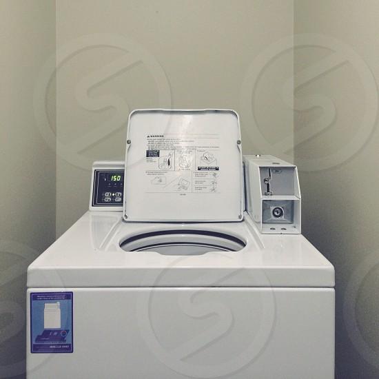 white top load washing machine near wall photo