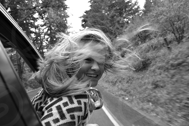 woman on vehicle on road during daytime at grayscale photography photo