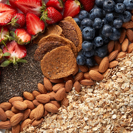 Close-up of a set of ingredients oatmeal granola almonds snacks blueberries and strawberries halves top view. Healthy vitamin breakfast photo