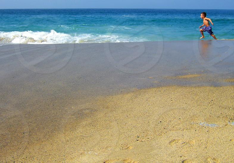 Little boy runs alone on an empty beach parallel to the ocean photo