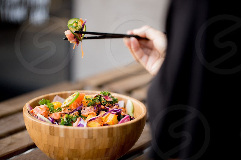 person eating vegetable salad with black chopstick photo